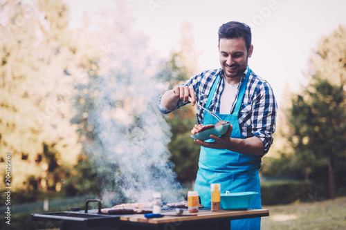 Handsome man preparing barbecue - 204129961