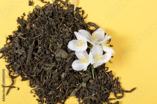 zielona herbata i jaśminowy świeży kwiat leżą na stole