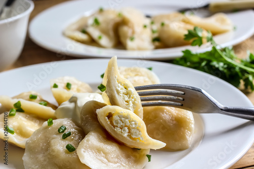 Russian, Ukrainian or Polish dish: varenyky, vareniki, pierogi, pyrohy. Dumplings, filled with cottage cheese and served with sour cream. Top view - 204144708