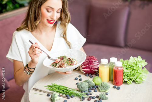 Woman with healthy food and smoothies indoors