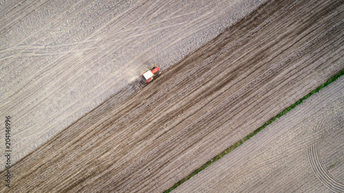 Fotobehang Donkergrijs Tractor working on field seen from the drone