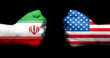 Постер, плакат: Flags of USA and Iran painted on two clenched fists facing each other on black backgroundTensed relationship between USA and Iran concept