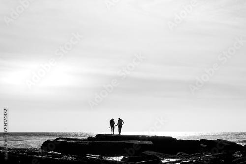 Plexiglas Zee zonsondergang Couple on rocks