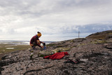Young woman in touristic clothes making coffee on the nature  in Iceland