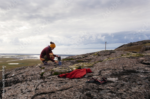 Fotobehang Cappuccino Young woman in touristic clothes making coffee on the nature in Iceland