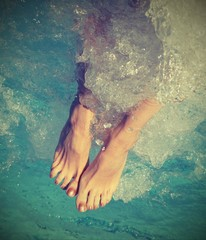 feet of girl during the whirlpool therapy in the spa pool with v