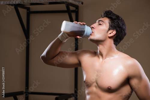 Wall mural Man with nutrient supplements in sports gym