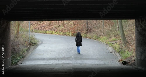 Fridge magnet Woman walking under a bridge in 4K. Lonely melancholic sad atmosphere concept of destiny journey road direction