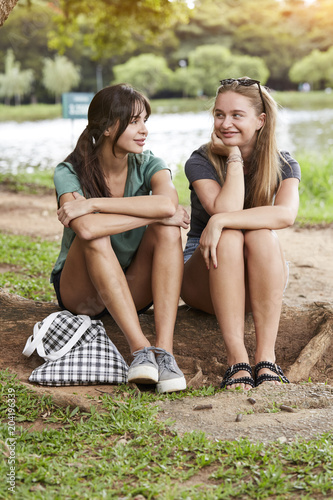 Fototapeta Girlfriends relaxing together in park