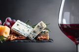 Glass of red wine with various cheeses . - 204202586