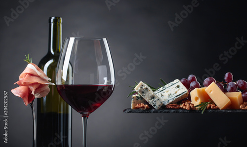 Fototapeta Glass of red wine with various cheeses , fruits and prosciutto.