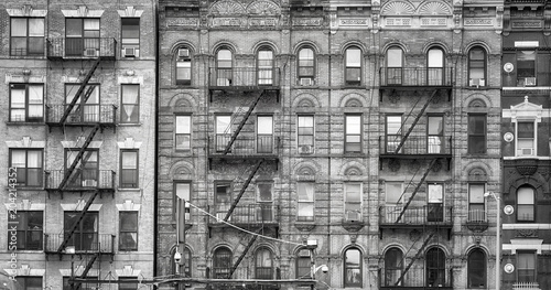 Black and white picture of old buildings with fire escapes, one of the New York City symbols, USA. - 204214352