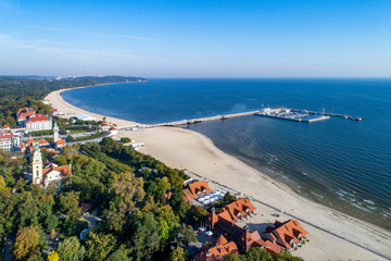 Sopot resort in Poland. Wooden pier (molo) with marina, yachts, beach, old lighthouse, church, vacation infrastructure, hotels, park and promenade. Far view of Gdynia. Aerial view at sunrise