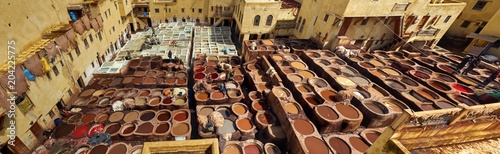 Leather factory for traditional leather painting in stone vats with paint in city of Fez, Morocco, panoramic.