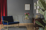 Navy blue armchair next to gold table with pink flowers in elegant living room interior