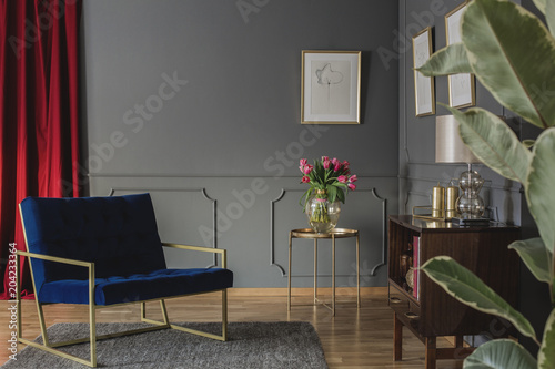 Fridge magnet Navy blue armchair next to gold table with pink flowers in elegant living room interior