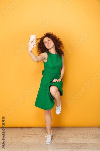 Full length portrait of a pretty redhead woman in dress