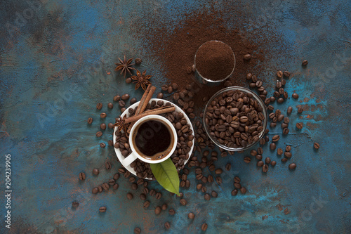 Сoffee in white cup сoffee beans and ground powder on brown background. Top view