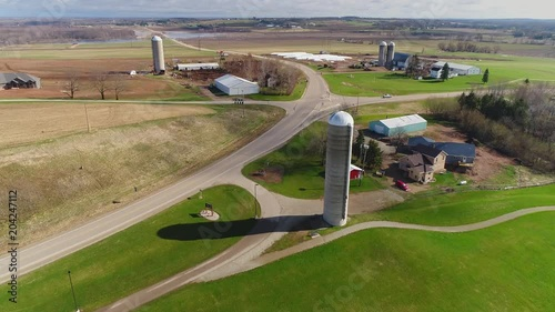 Scenic country road with rural farms on a windy spring day, aerial view.