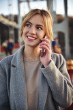 Cute smiling young woman talking on phone standing on the bride.