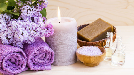 Spa setting with lilac, towels and candle, still life of wellness spa © marrakeshh