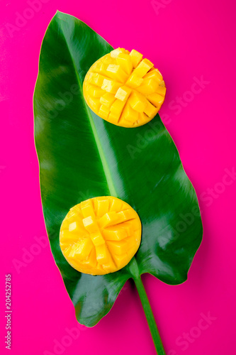 Plexiglas Roze Creative layout made of summer tropical fruits mango and tropical leaves on pink background. Flat lay. Tropical food concept.