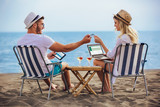 Happy smiling couple surfing the net and enjoy the summer at tropical beach using laptop, digital tablet and credit card