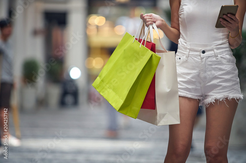 Fototapeta Asian Woman holding shopping bags in hand and feeling happiness.
