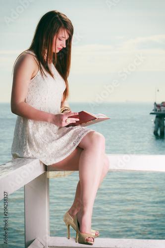 Woman sitting on hurdle near sea, reading book