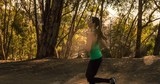 Athletic Woman Working Out. Running along a path through the woods. - 204258707