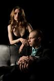 Gorgeous couple shot on black sofa at night