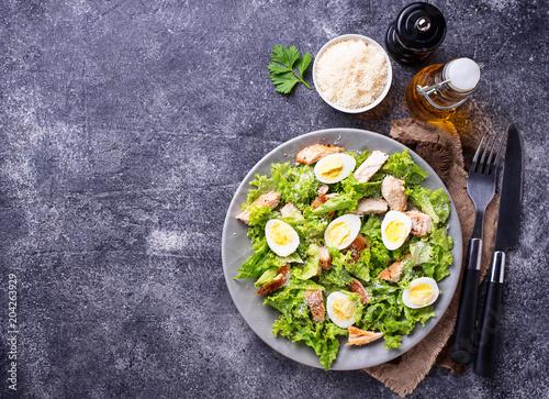 Fototapeta Caesar salad with eggs, chicken and parmesan