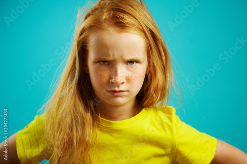 Portrait of disgruntled child girl with furrowed eyebrows, expressing dissatisfaction or disagreement, demonstrates difficulty of character and capricious mood, stood upset kid on blue isolated.