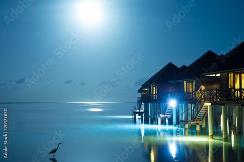 Plexiglas Strand Sunset on Maldives island, luxury water villas resort and wooden pier. Beautiful sky and clouds and beach background for summer vacation holiday and travel concept