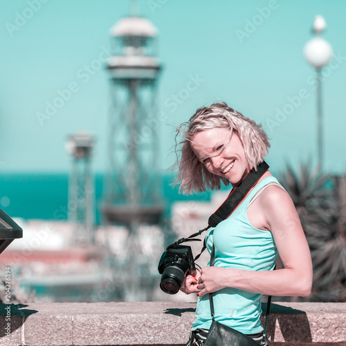 Female traveler standing with camera against the background of the port of Barcelona Poster