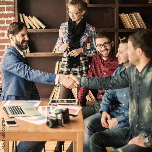 handshake business partners at a meeting in creative office