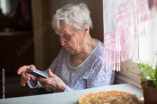 An elderly woman sits with a smartphone in her hands.