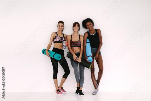 Wall mural Sporty girls with fitness mat having a break