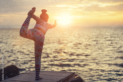 Woman Pose Yoga On Wooden Pier At Sea Side Against Beautiful Sun