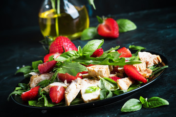 Salad with arugula, strawberries and chicken, dark background, selective focus
