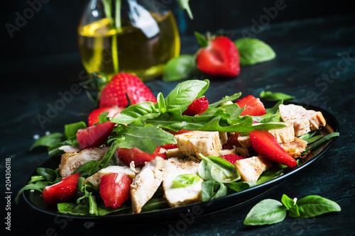 Fototapeta Salad with arugula, strawberries and chicken, dark background, selective focus