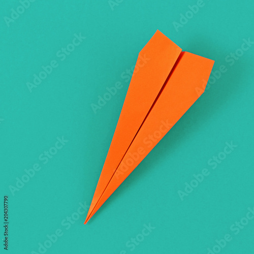 Flat lay colorful paper plane on pastel turquoise background. Top view creative travel background concept © kucherav