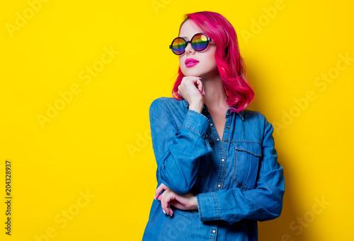 Młoda różowa włosiana dziewczyna w okularach przeciwsłonecznych i błękitnej koszula. Portret na żółtym tle