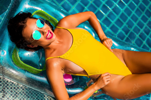 Foto Murales amazing beautiful girl in a yellow bikini air mattress swims in the pool of a luxury hotel, summer vacation, happiness, travel, smile joy