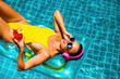 amazing beautiful girl in a yellow bikini air mattress swims in the pool of a luxury hotel, summer vacation, happiness, travel, smile joy, listening to music, drinking cocktail