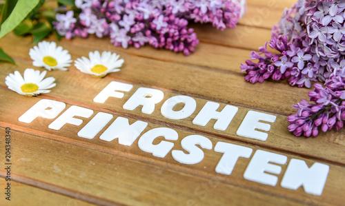 Frohe Pfingsten Wörter auf einem Holtbrett mit Flieder Blumenstrauß - 204348340