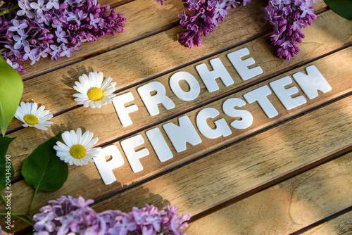 Frohe Pfingsten Wörter auf einem Holtbrett mit Flieder Blumenst - 204348390