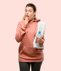 Young sport woman wearing workout sweatshirt covers mouth in shock, looks shy, expressing silence and mistake concepts, scared © Aaron Amat