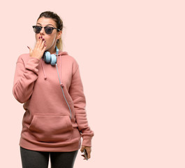 Young sport woman with headphones and sunglasses looking at camera showing tong and making victory sign with fingers © Aaron Amat
