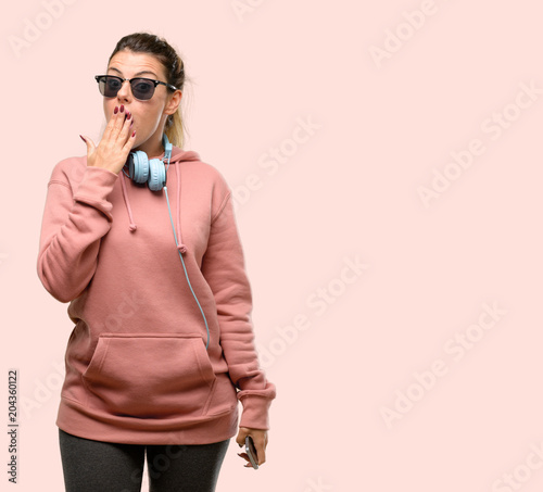 Wall mural Young sport woman with headphones and sunglasses looking at camera showing tong and making victory sign with fingers